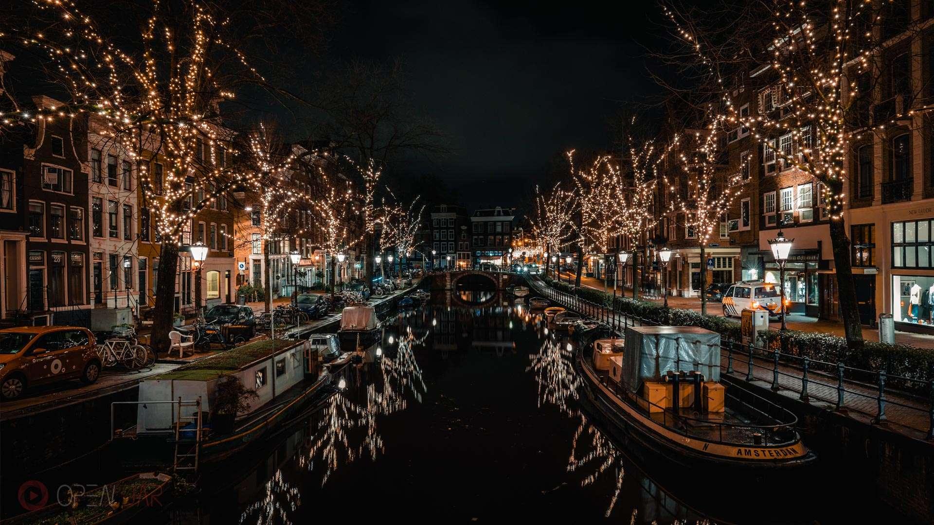 Spiegelung von Lichterketten im Kanal in Amsterdam