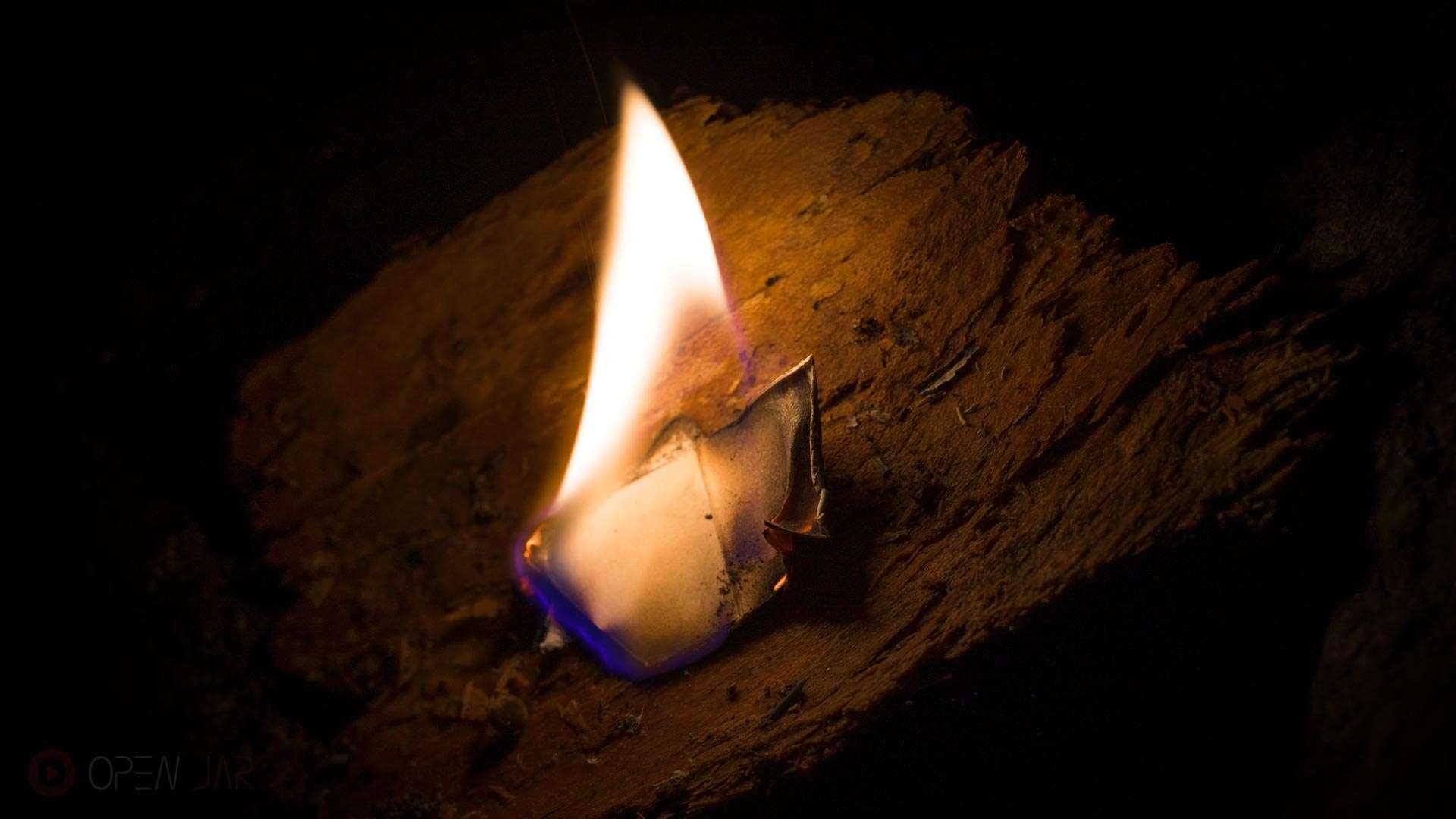 Ein Stück Papier brennt auf einem Stück Baumrinde